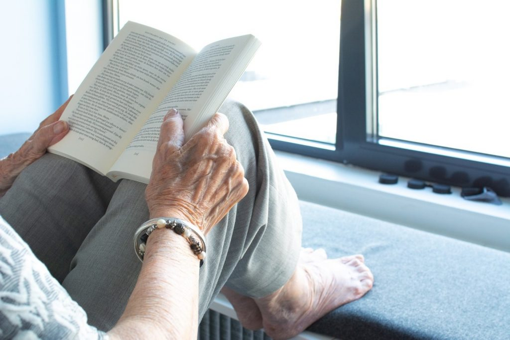 Old lady reading a book at a home care